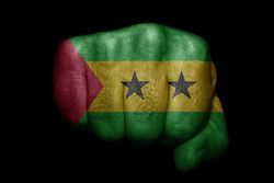 Flag of Sao Tome and Principe painted on strong fist on black background