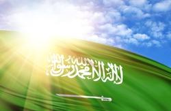 flag of Saudi Arabia against the blue sky with sun rays