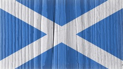 Flag of Scotland on a dry wooden surface. Patriotic vintage backdrop. Rough board with cracks. The official Scottish symbol. Edge of the flag has faded like light vignetting