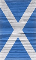 Flag of Scotland on a dry wooden surface. Vertical vintage backdrop. Rough board with cracks. The official Scottish symbol. Edge of the flag has faded like light vignetting