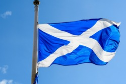 Flag of Scotland (Saltire or the Saint Andrew's Cross) blowing in the wind towards clear blue sky in a sunny day