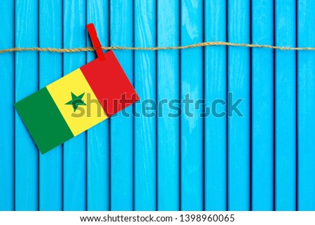 Flag of Senegal hanging on clothesline attached with wooden clothespins on aqua blue wooden background. National day concept. #1398960065