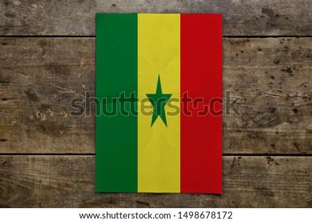 Flag of Senegal on wooden board. Paper Flag of Senegal on wooden table. #1498678172