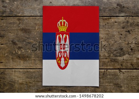 Flag of Serbia on wooden board. Paper Flag of Serbia on wooden table. #1498678202