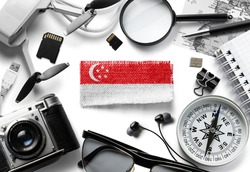Flag of Singapore and travel accessories on a white background.