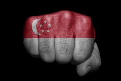 Flag of Singapore painted on strong fist on black background
