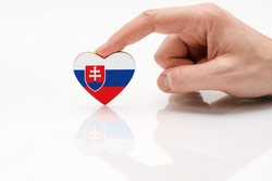 Flag of Slovakia. Love and respect Slovakia. A man's hand holds a heart in the shape of the Slovakia flag on a white glass surface. The concept of Slovak patriotism and pride.