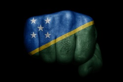 Flag of Solomon Islands painted on strong fist on black background