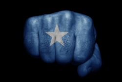 Flag of Somalia painted on strong fist on black background