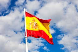 Flag of Spain over blue sky moving in wind