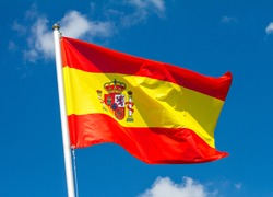 Flag of Spain waving in the wind on flagpole against the sky with clouds on sunny day, close-up