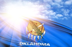 flag of State of Oklahoma against the blue sky with sun rays