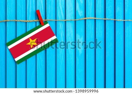 Flag of Suriname hanging on clothesline attached with wooden clothespins on aqua blue wooden background. National day concept. #1398959996