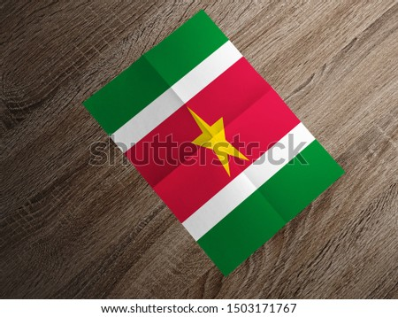 Flag of Suriname on paper. Suriname Flag on wooden table. #1503171767