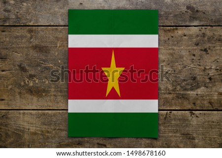 Flag of Suriname on wooden board. Paper Flag of Suriname on wooden table. #1498678160