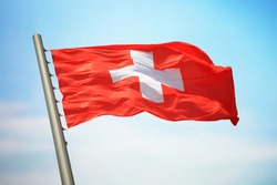 Flag of Switzerland against the background of the blue sky