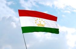 Flag of Tajikistan in front of blue sky