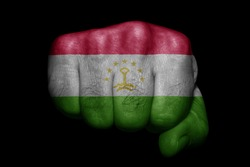 Flag of Tajikistan painted on strong fist on black background