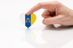 Flag of the Canary Islands. Love and respect Canary Islands. A man's hand holds a heart in the shape of the Canary Islands flag on a white glass surface. The concept of patriotism and pride.