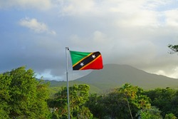 Flag of the Federation of St Kitts and Nevis floating in front of the Nevis volcano