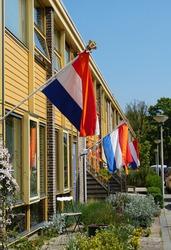 Flag of the Netherlands and several orange decorations during king's day, an official national holiday celebrating the kings birthday.