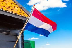 Flag of the Netherlands waving in the wind against blue sky and old dutch house in Zaanse Schans village.