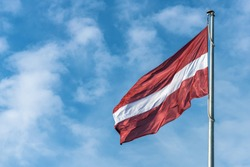 Flag of the Republic of Latvia. Flag of Latvia against the blue sky. Copy space.