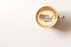 Flag of the United States of America in the form of territorial borders on a cappuccino coffee cup close-up