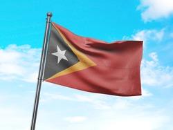 Flag of Timor Leste on Flag Pole in Blue Sky. Timor Leste Flag for advertising, celebration, achievement, festival, election. The symbol of the state on wavy cotton fabric.