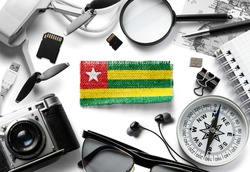 Flag of Togo and travel accessories on a white background.