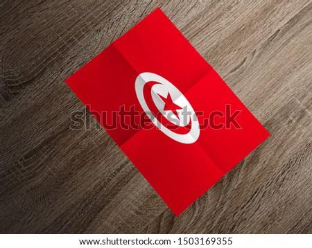 Flag of Tunisia on paper. Tunisia Flag on wooden table. #1503169355