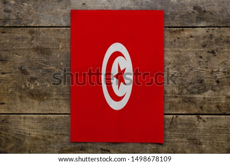Flag of Tunisia on wooden board. Paper Flag of Tunisia on wooden table. #1498678109