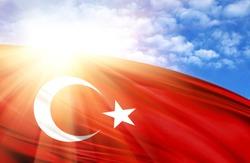 flag of Turkey against the blue sky with sun rays