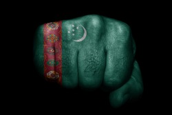 Flag of Turkmenistan painted on strong fist on black background