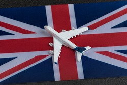 Flag of United Kingdom and toy airplane. Air travel in UK. Resuming flights after quarantine.