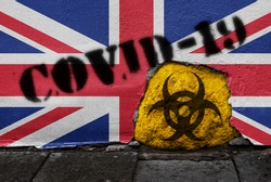 Flag of United Kingdom on the wall with covid-19 quarantine symbol on it. 2019 - 2020 Novel Coronavirus (2019-nCoV) concept, for an outbreak occurs in UK.