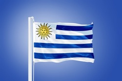 Flag of Uruguay flying against a blue sky.