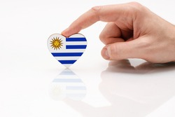 Flag of Uruguay. Love and respect Uruguay. A man's hand holds a heart in the shape of the Uruguay flag on a white glass surface. The concept of Uruguayan patriotism and pride.