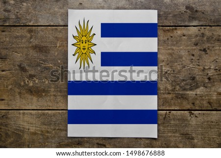Flag of Uruguay on wooden board. Paper Flag of Uruguay on wooden table. #1498676888