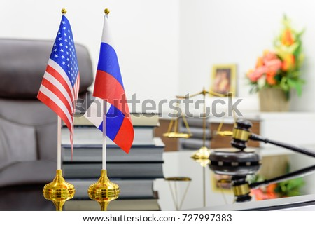 Flag of USA and Russia put together on a table with books, gavel and a balance scale of justice. A symbol of cooperation between Washington and Moscow i.e. military dialogue, diplomatic negotiation. #727997383