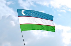 Flag of Uzbekistan in front of blue sky