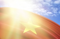 flag of Vietnam against the blue sky with sun rays