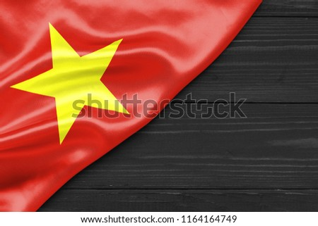Flag of Vietnam and place for text on a dark wooden background #1164164749