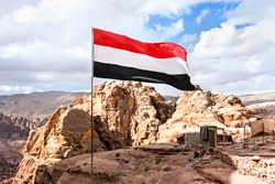 flag of Yemen is flying in the wind against a cloudy sky in the mountains.
