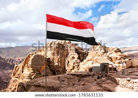 flag of Yemen is flying in the wind against a cloudy sky in the mountains. Stock fotó ©