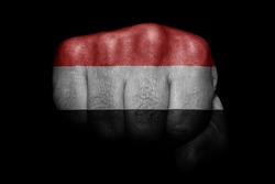 Flag of Yemen painted on strong fist on black background
