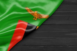 Flag of Zambia and place for text on a dark wooden background