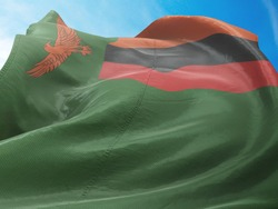 Flag of Zambia on Flag Pole in Blue Sky. Zambia Flag for advertising, celebration, achievement, festival, election. The symbol of the state on wavy cotton fabric.