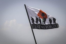 Flag on a pole with a poppy and silhouette of soldiers with the words lest we forget remembrance day