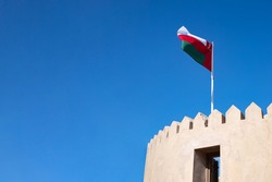 Flag on roof of fort in Oman. Blue sky copy space.